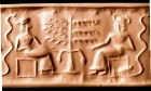 Impression from a greenstone cylinder seal, showing a serpent and a tree with two figures, probably deities