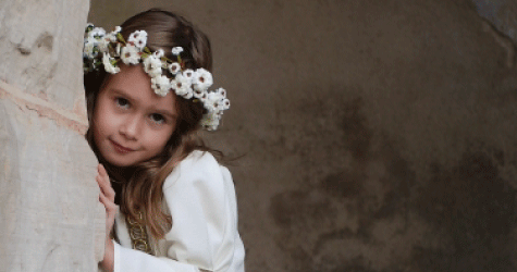 Small girl with garland of white flowers in her hair