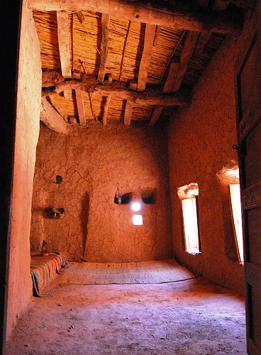Interior of a clay brick house with wooden and bark roofing