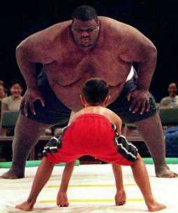 A David and Goliath situation: sumo wrestler towers over a small boy