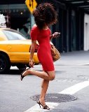 Woman in red dress with New York taxi