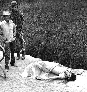 Vietnam photograph. The woman has been raped and murdered. The men smile and pose for the photographer.
