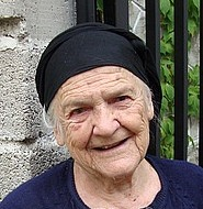 An elderly woman with a wise and loving face