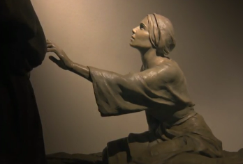 The woman reaches up towards Jesus, barely touching him