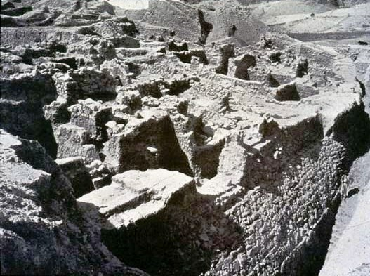 Excavated revetment wall at ancient Jericho; notice the human figure at the bottom right of the 19th century photograph