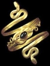 Bad Bible Women: Gold spiral bracelet of two snakes whose tails are tied in a Hercules knot that is decorated with a garnet in a bezel setting; from Eretria, on the island of Euboea, 4th–3rd century BC