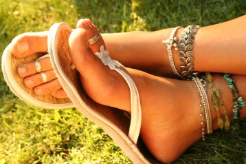 Woman's manicured feet with sandals and foot and ankle jewelry