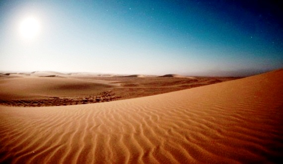Photograph of a sand desert with blazing sun