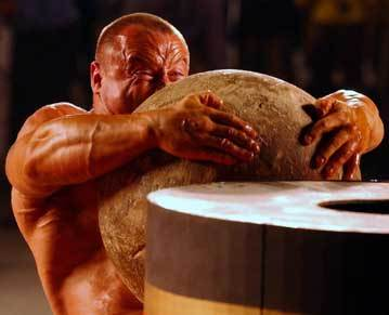 Bible Soldiers & Warriors: Samson. Photograph of an exceptionally strong man lifting a stone ball onto a high wooden stand