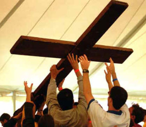 Young people raising a wooden cross