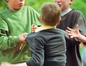 Boys bullying a smaller boy