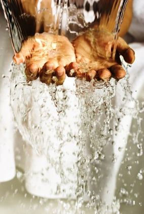 Pure water flowing over a pair of outstretched hands