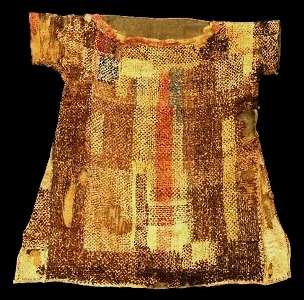 A child's garment found by archaeologists south of Cairo. It was woven from coloured wools as a single piece of cloth folded over at the shoulders, It appears to have been darned for recycling