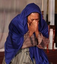 A kneeling woman pleads for help