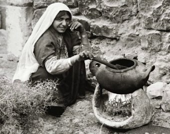 Bible food: Middle Eastern woman cooking on a portable stove