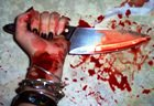Blood-spattered woman's hand holding a sharp knife