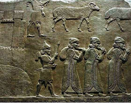 High-ranking (denoted by their long fringed robes) Assyrian officials carry away the loot from the